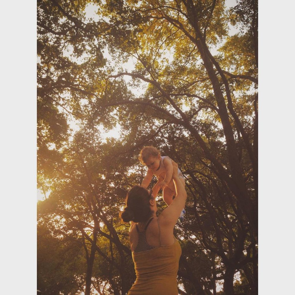 Seattle Washington Graphic Designer Christina Joan in a park holding her child up to trees.